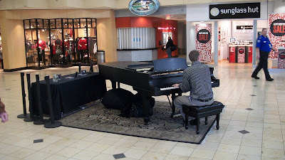 A piano set up in the middle of the airport, with a guy playing very lovely songs for the people walking by.