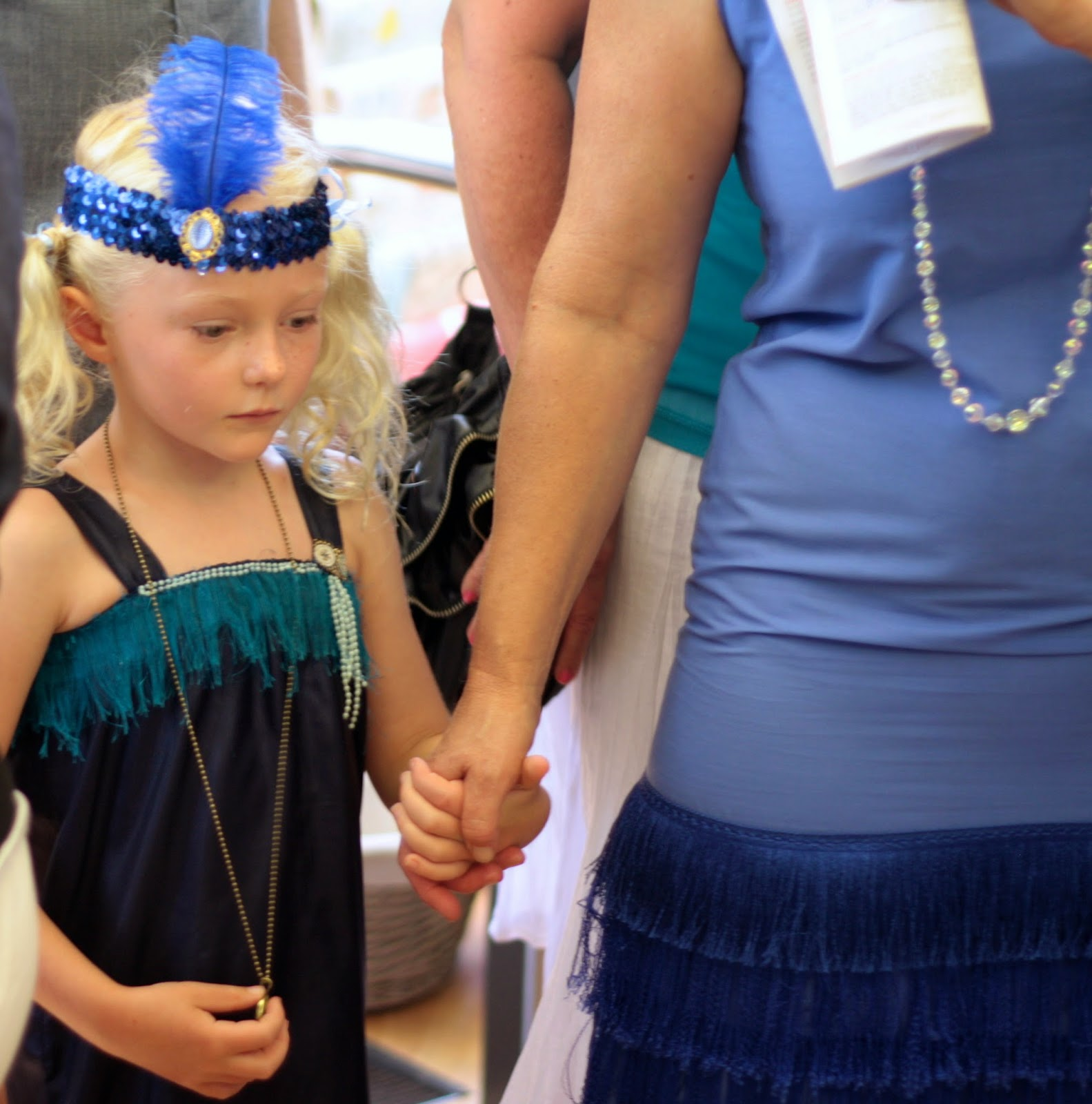 Cute kid wearing a beaded flapper headband with feather.