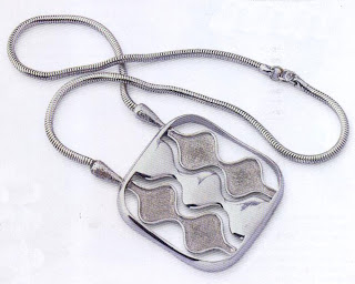 Again in modern materials, in this case a chrome-plated snake chain with an aluminum pendant, this pendant displays aspects of free-form organic art.
