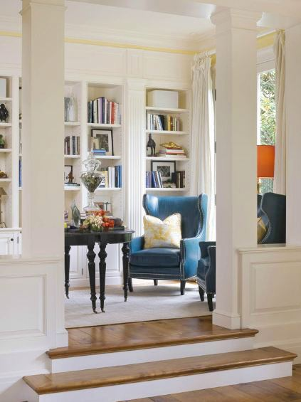 Library in a san francisco mansion with two blue wingback chairs with nail head trim, a black table, wide paneled wood floor, white built in book shelves, white floor length curtains and a white area rug