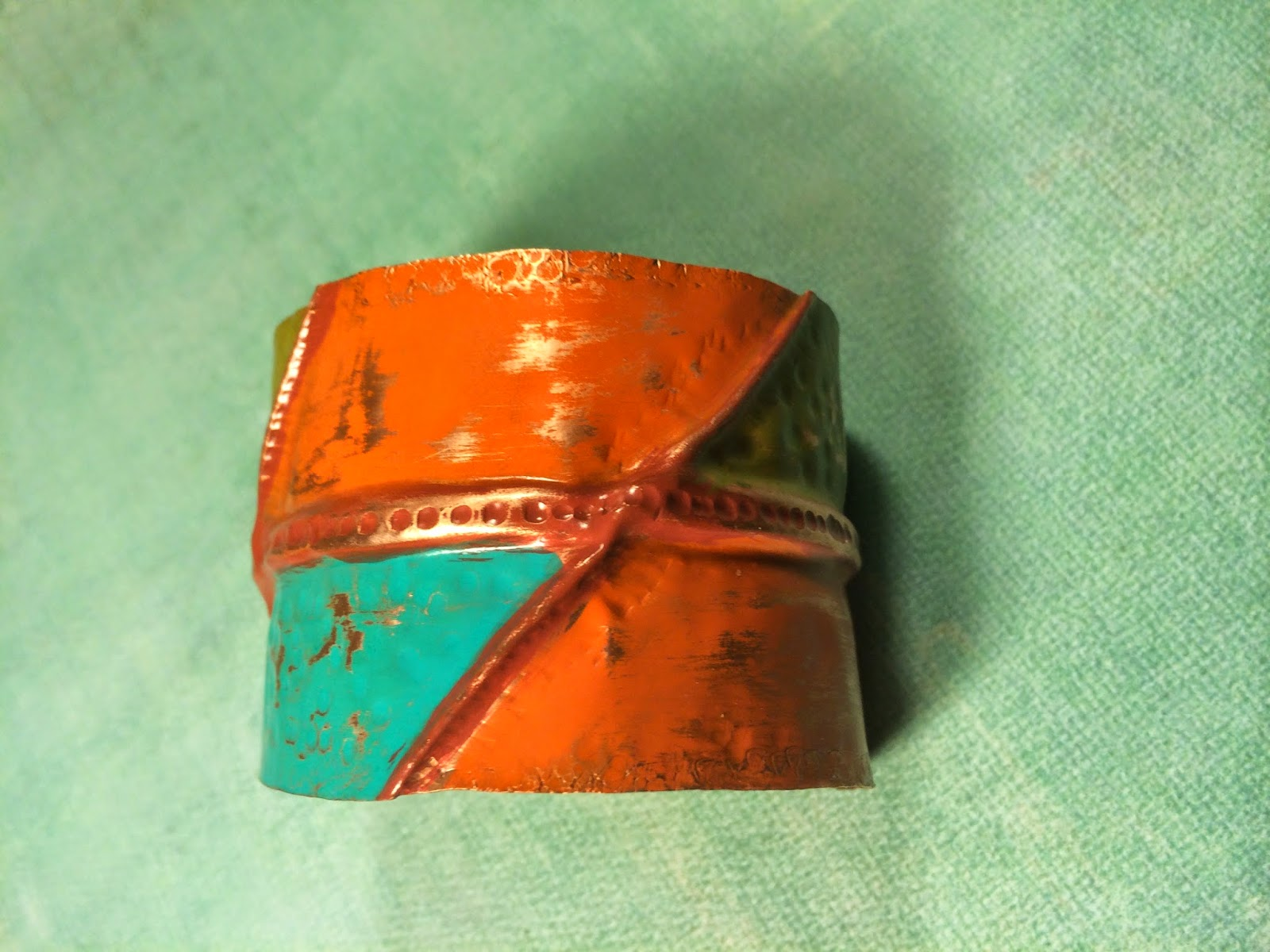 Top of fold formed copper cuff with texture and multi colored patina