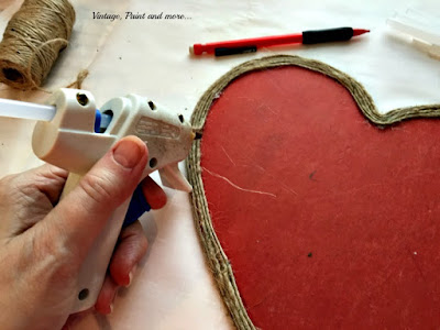 gluing twine onto a wooden heart