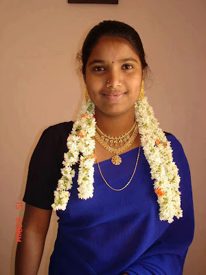 Traditional Tamil girl in blue saree with head full of jasmine flowers.