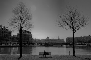 """Cette image en noir et blanc montre un homme seul sur un banc dans ce qui semble un parc situé dans une ville. Le banc est entouré de deux arbres sans feuilles et se trouve devant un lac. Au loin nous pouvons distinguer des bâtiments surplombés par un ciel uniformément gris. Cette photographie présente de grandes qualités esthétiques notamment grâce à la dispoistion rigoureuse et symétrique des éléments qui la composent. Le banc ets parfaitement centré et le personnage assis desuus l'est également lui-même. De même les arbres sont à égale distance du banc et du personnage. Cette superbe photographie d'où se dégage une grande mélancolie illustre le non moins mélancolique et superbe poème """"Le dernier mot"""" du Marginal Magnifique dans lequel le grand poète moderne annonce sa volonté de se retirer de la société plutôt que d'être broyé par le système qu'on ne peut vaincre. L'image empreinte de solitude et de mélacolie fait parfaitement écho aux sentiments ressentis à la lecture de ce magnifique poème, sentiments de désespoir et de résignation solitaire face à sa propre faiblesse contre la dureté et l'injustice de la société."""