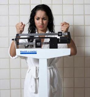 كيف تتجنبين زيادة الوزن بدون ريجيم - فتاة تقف على ميزان حزينة