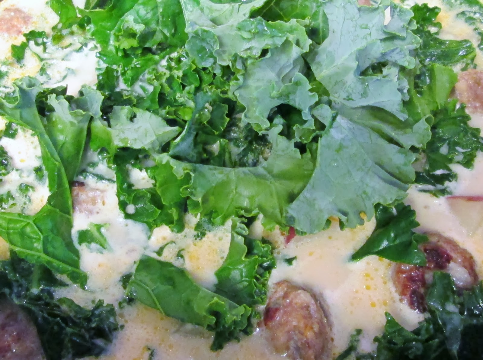 Kale steams on top of the creamy sausage and potato stock.
