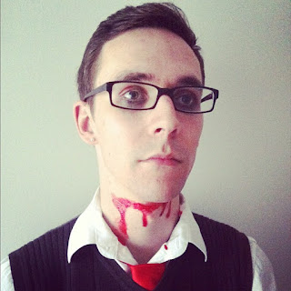 Josh, wearing a waistcoat, collared shirt and tie, staring vacantly into the middle distance, with his throat slashed.