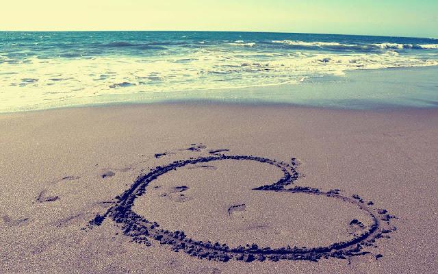 Foto van een getekend liefdes hartje in het zand