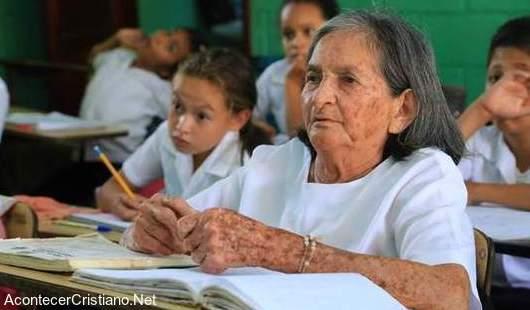 Anciana estudia en escuela para aprender a leer la Biblia