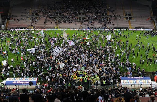 Juventus fans run onto the pitch to celebrate after the Scudetto