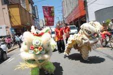 Na foto, duas alegorias confeccionadas de pelúcia branca, com olhos e boca bem pronunciados, ladeadas por dois rapazes em traje vermelho e preto, tipicamente chinês. Dá para ver que o conjunto está bem no meio da rua, como acontece com qualquer desfile aberto.
