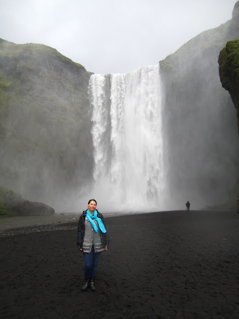 Woman standing near waterfall in Skogar, Iceland.