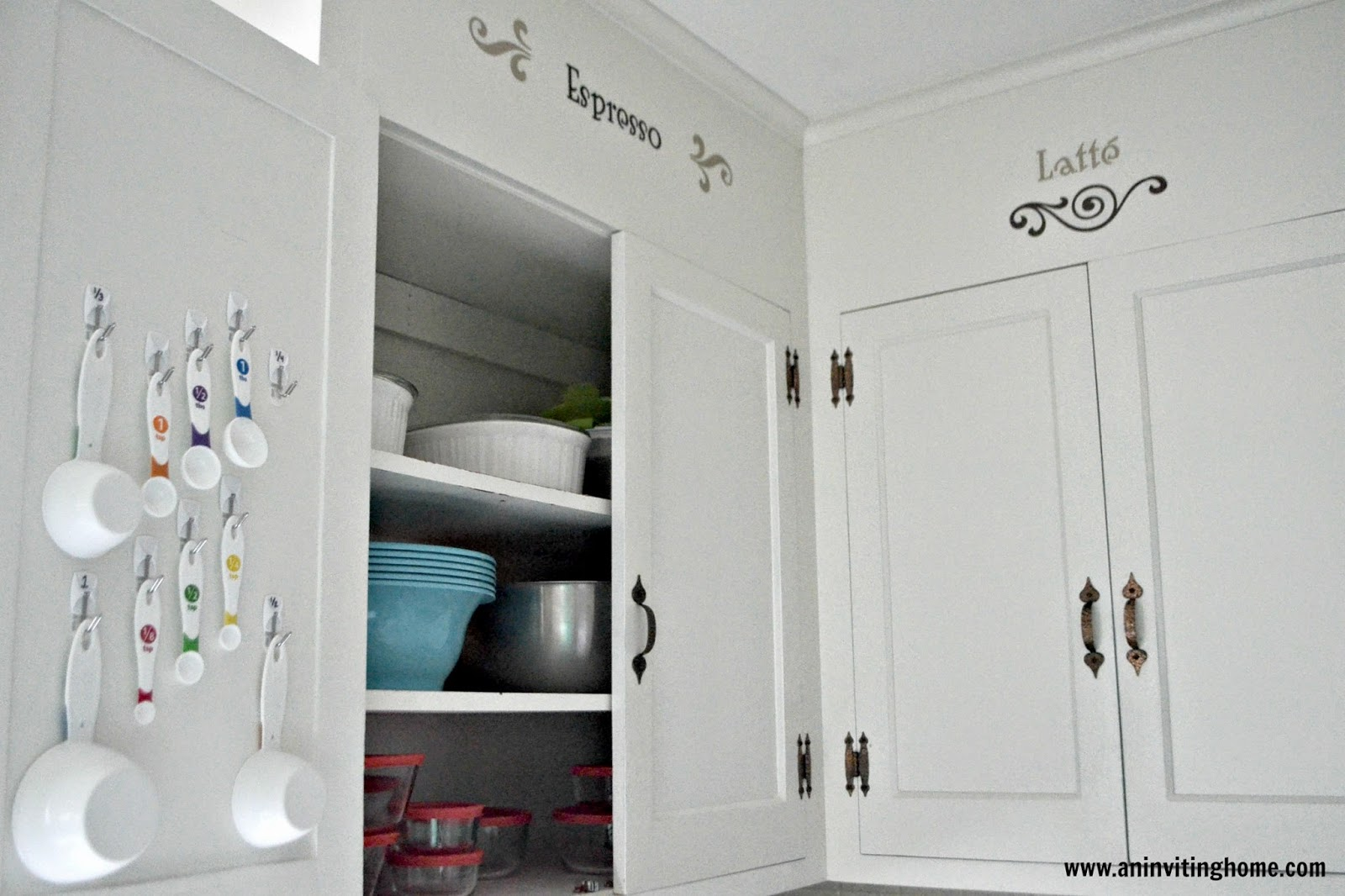 hang measuring cups and spoons on back of cupboard door