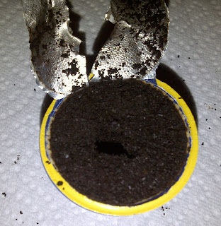 Lid removed from K-cup shows coffee grounds inside