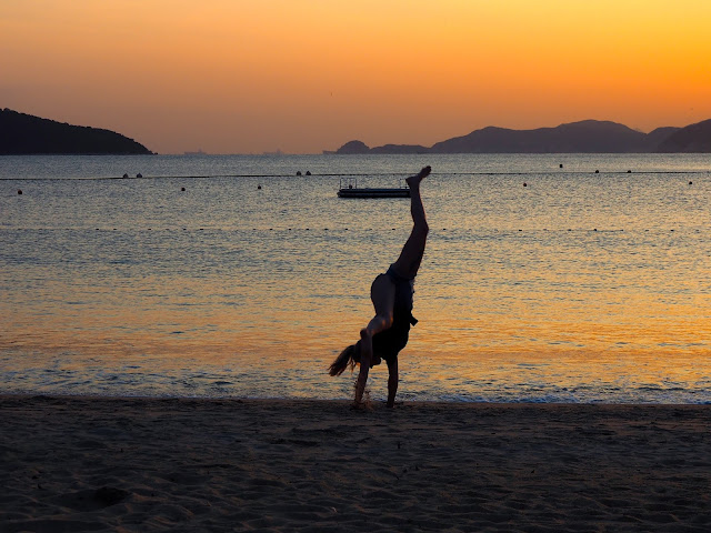 Silhouette of a girl doing a cartwheel in the sand at sunset on Repulse Bay Beach, Hong Kong