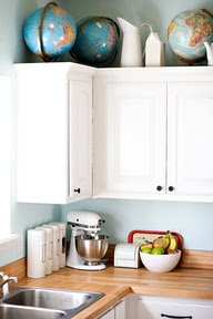 mylittlehousedesign.com globes on top of white kitchen cabinets