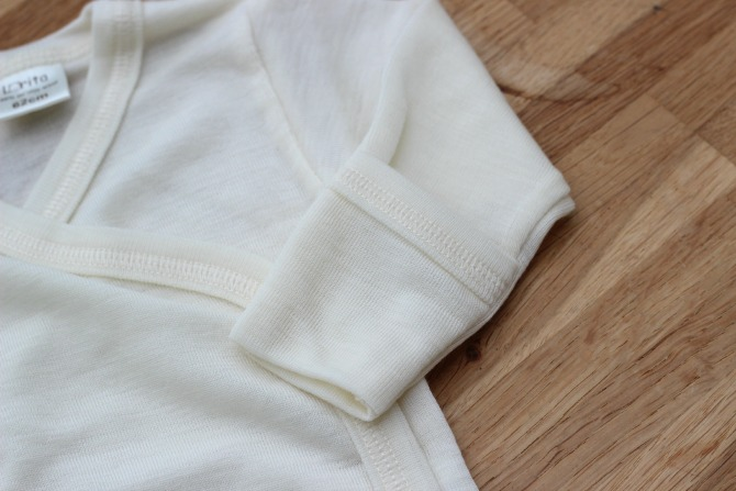 Detail of scratch mitts on the kimono style body suit