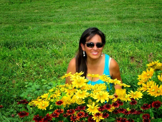 Woman sitting in front of yellow daisies