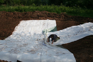 Laying the bentonite liner in a wildlife pond
