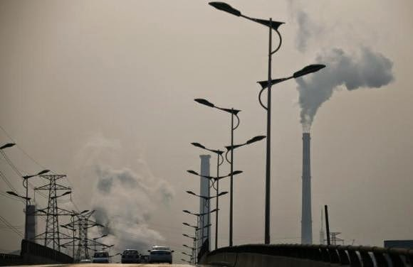 Smoke rises from chimneys of a steel plant next to a viaduct on a hazy day in Tangshan, Hebei province February 18, 2014. (Credit: Reuters/Petar Kujundzic) Click to Enlarge.