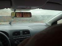 foto van de voorruit van de auto met ons in de achteruitkijkspiegel op de achtergrond de plensbui