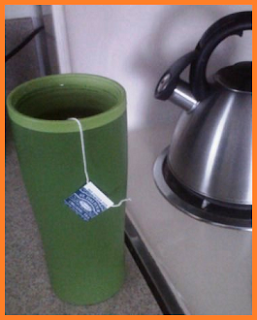 A tea bag floating within the filled green thermal mug, with a kettle sitting off to the side.