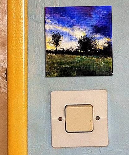 photo of landscape art above a standard light switch