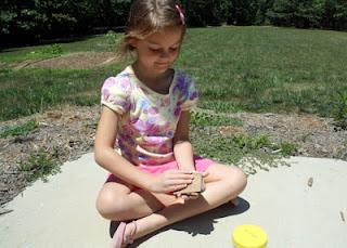 Tessa rubbed sandpaper on a mock rock.