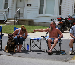 shirtless guy and dog at parade, long beard