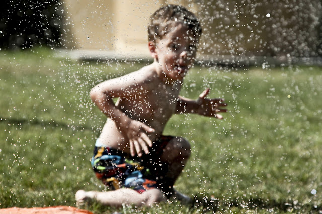 A little boy getting up from a turn on a slip'n slide.