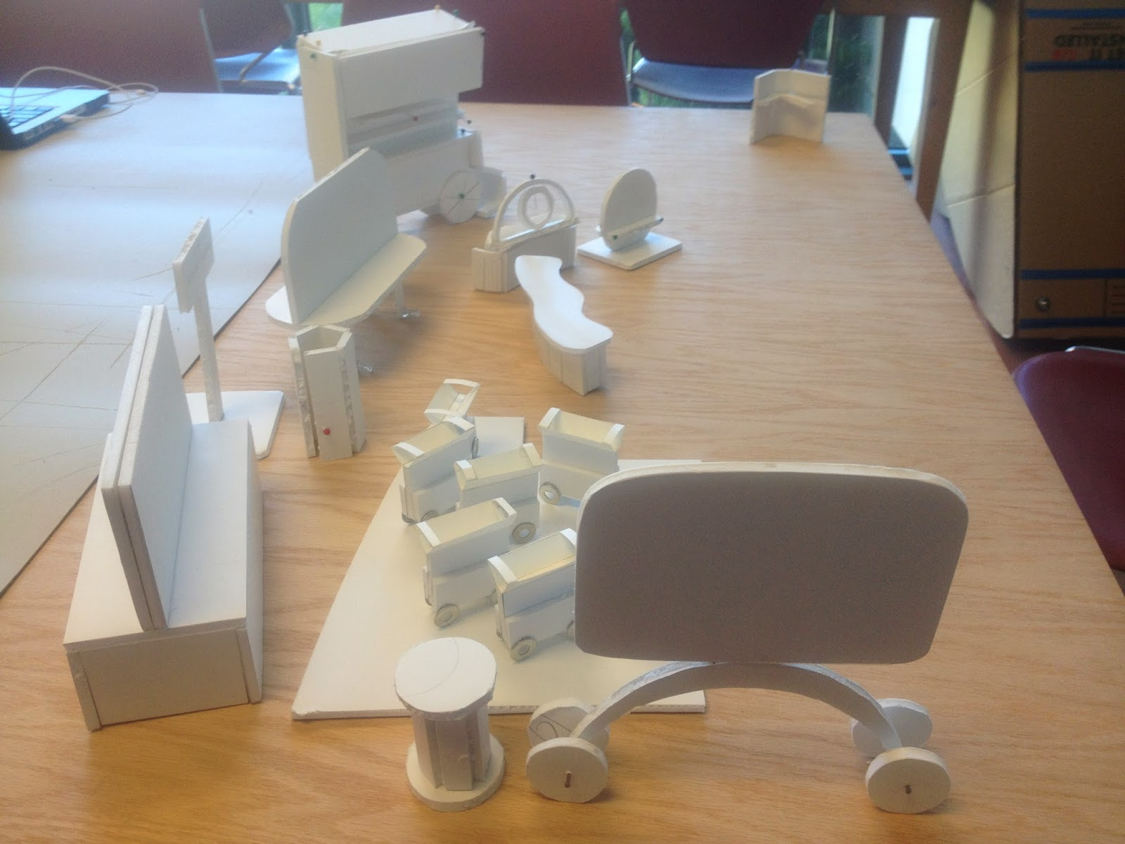 The image shows a side view of the white foam core model mockups grouped together on a table.