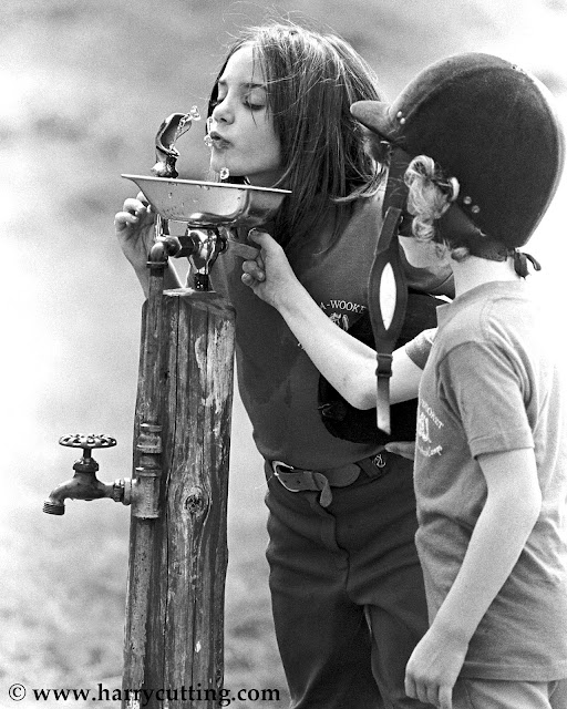 Young girls drinking at fountain at horseback riding camp in Vermont.