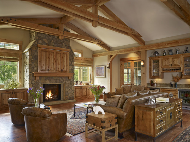 Wide Living Room with Brown Sofas and a Low Table facing the Stone Rustic Fireplace Mantels