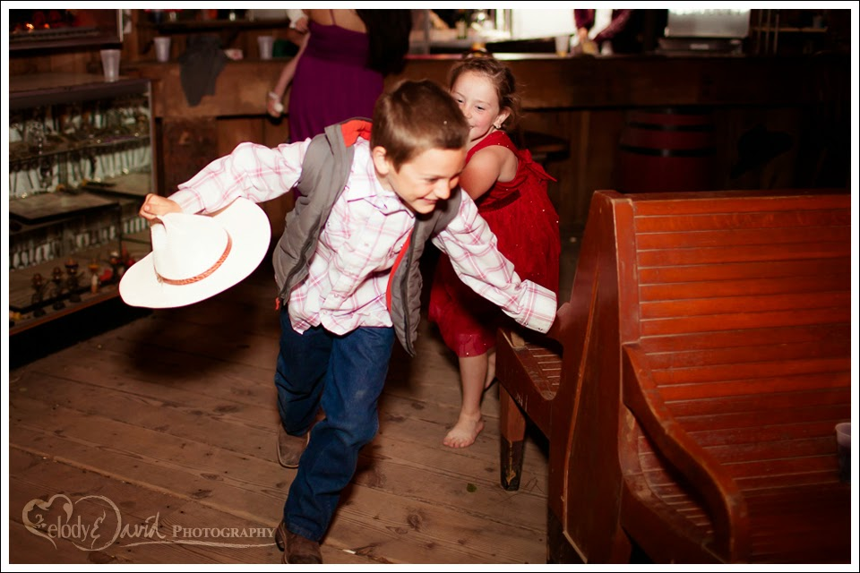 Flowergirl chases a dance partner at the wedding reception.