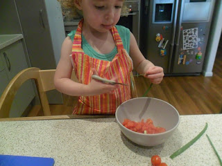 Young girl using scissors to snip herbs for the salsa