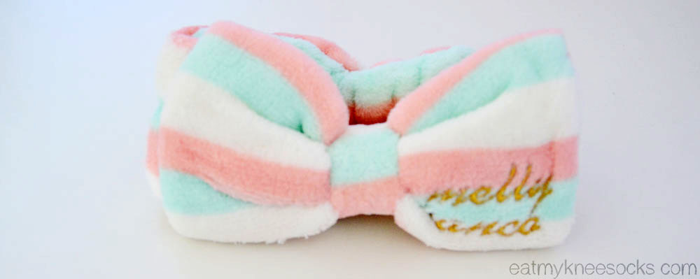 Love Shoppingholics' cute bow headband features pastel stripes and embroidered text.
