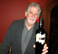 Photo of winemaker Tom Eddy with a bottle of his wine.