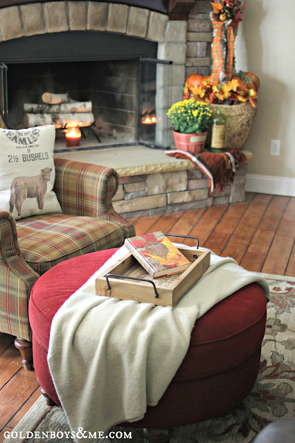 Walden book on ottoman by plaid chair by stone fireplace, part of Fall Home Tour via www.goldenboysandme.com