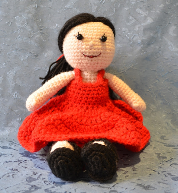 Kwokkie Doll seated in her red sundress, front view. Her straight black hair is tied back in a low ponytail with a red ribbon of yarn.