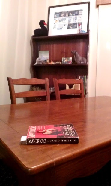 Wooden dining table with two wooden chairs behind and a small hutch behind them.