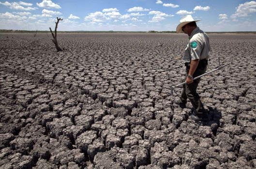 In this Aug. 3, 2011 file photo, Texas State Park police officer Thomas Bigham walks across the cracked lake bed of O.C. Fisher Lake in San Angelo, Texas. Global warming is rapidly turning America into a stormy and dangerous place, with rising seas and disasters upending lives from flood-stricken Florida to the wildfire-ravaged West, according to a new U.S. federal scientific report released Tuesday, May 6, 2014. (Credit: AP Photo/Tony Gutierrez) Click to enlarge.