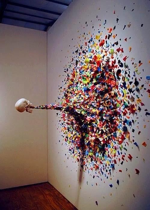 oeuvre d'art repésentant un crâne suspendu dans le vide vomissant des morceaux de couleur