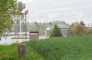 France - Suisse - entre Ferney Voltaire et Meyrin - premier plan borne frontière 72 - arrière plan aéroport de Genève Cointrain - le tunnel du LHC passe sensiblement à l'aplomb de la borne, le détecteur LHCb est situé légèrement à gauche de cette image.