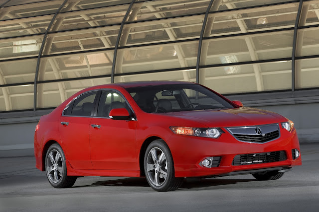 Front three-quarters view of red 2012 Acura TSX on rooftop garage in front of skylight