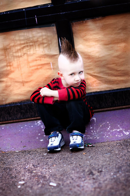 Tucson kid poses on a curb with his knees to his chest sporting a funky Mohawk for a Tucson Photographer
