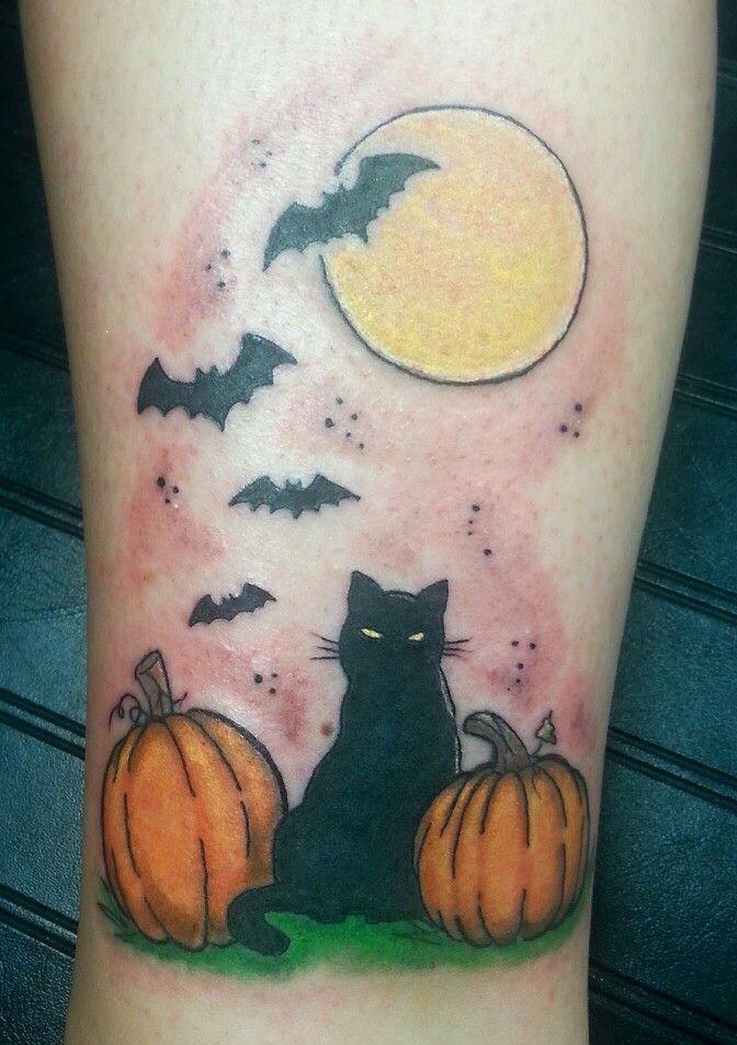 tatuaje de halloween con un gato entre dos calabazas