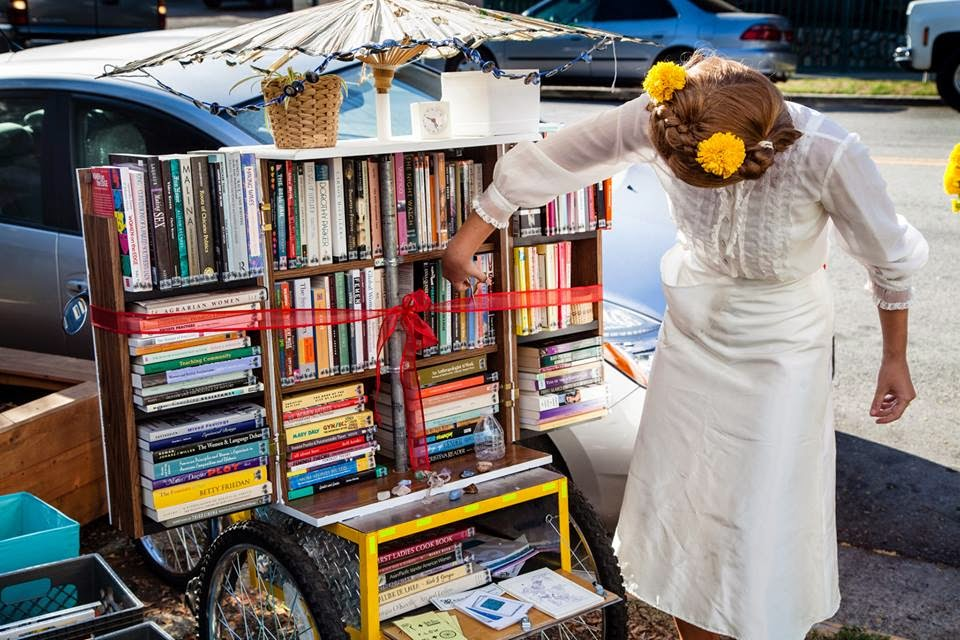 A woman cuts a ribbon that is stretched across a bookshelf on the back of a tricycle.