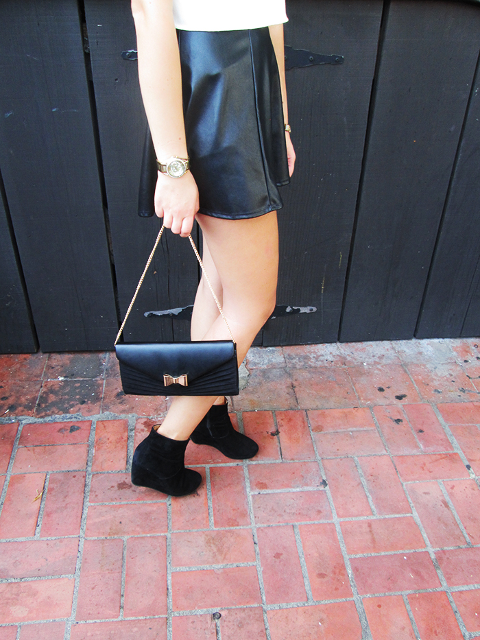 black leather skirt, black wedge heels, bow tie clutch