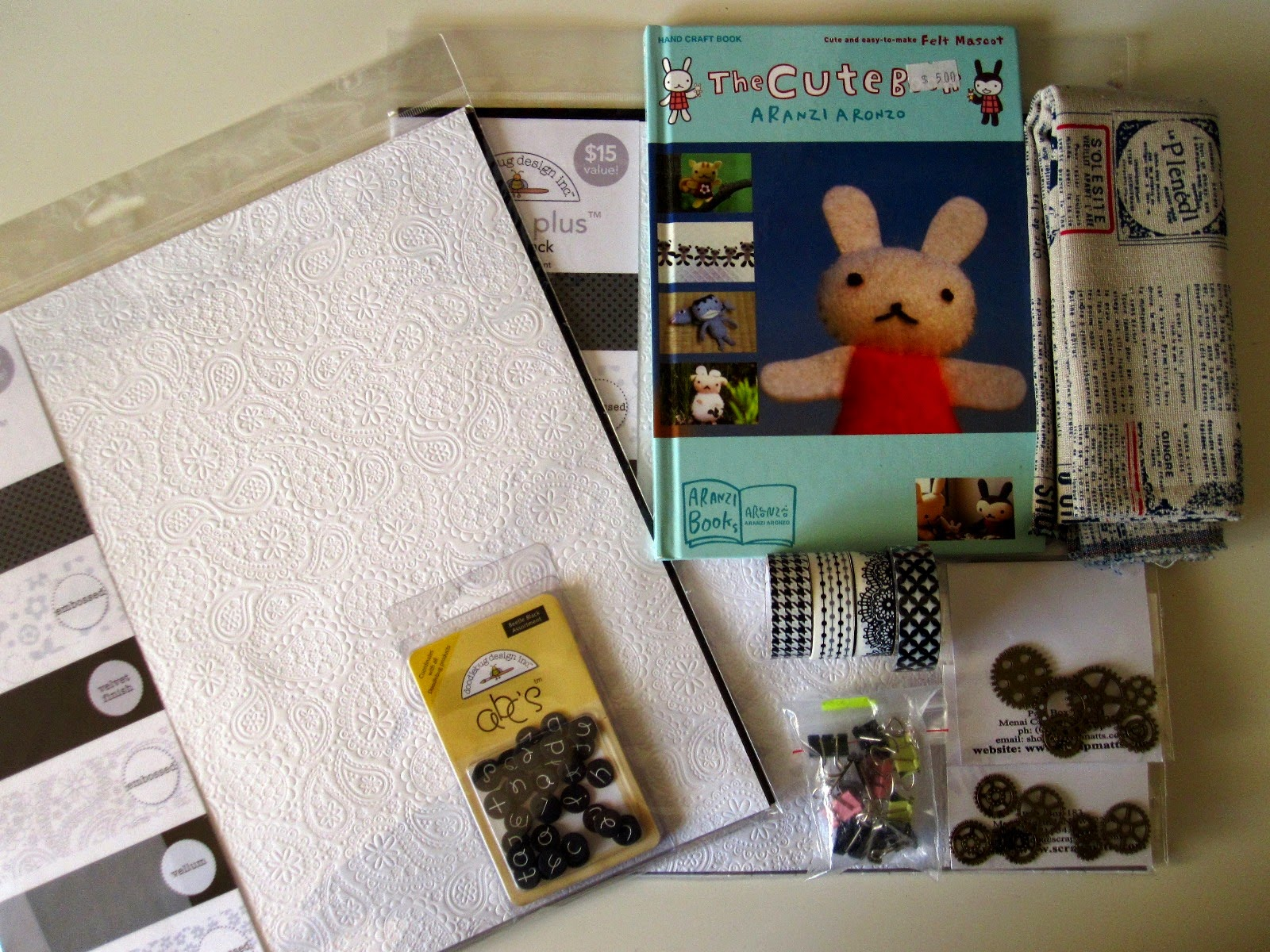 Selection of craft items including scrapbooking paper, fabric, washi tape, charms and a book.