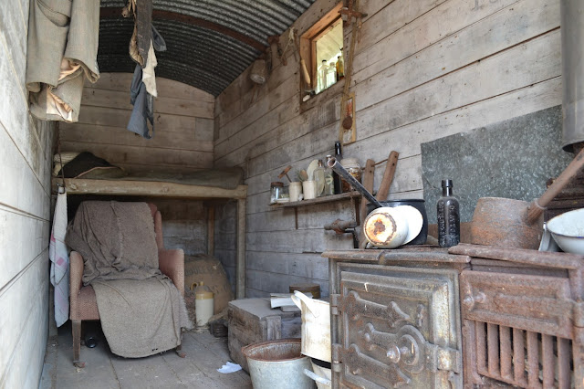 The inside of a Shepherds Hut with as bed and stove